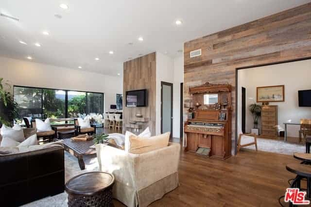 Classic room with a touch of wood elements. It includes beige and black sofas with white pillows complementing each other, hardwood flooring, wooden walls on white painted walls and a large glass panelled window that brings in the natural light.