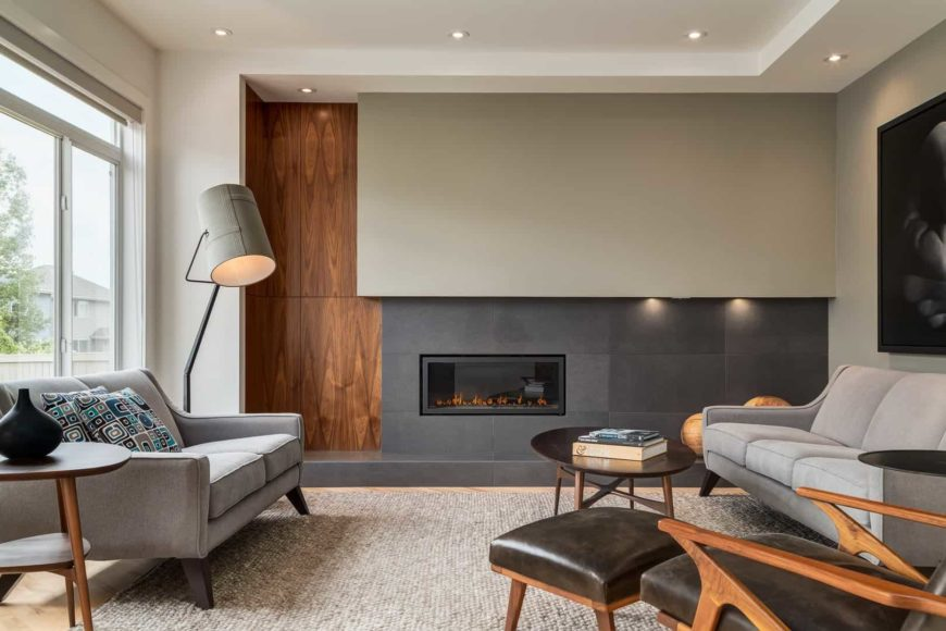 A modern living room with an elegant accent wall composed of walnut panel, gray painted wall and black tiled wall where a fireplace is mounted. Gray couches and a black recliner lounge chair paired with round coffee table sit on a gray rug. Recessed lighting and a lovely floor lamp add warmth to the room.