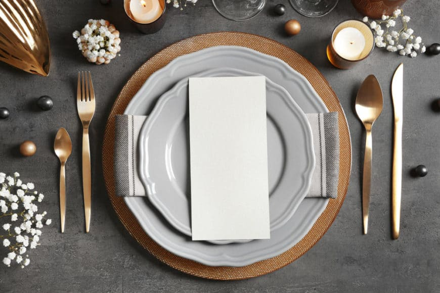 Dining table place setting with plate, utensils and more.