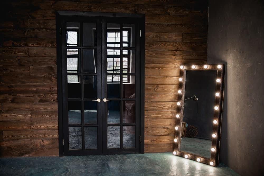Corner room with French doors and a makeup mirror on the floor.