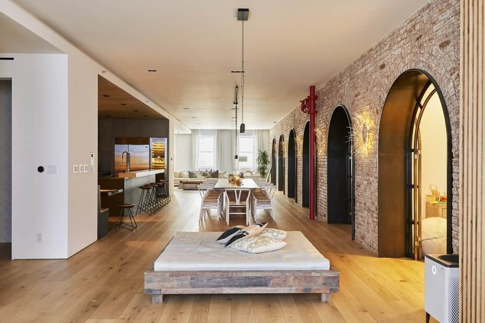 This angle of the large open floor plan showcases the red brick arches on the side of the dining and living room with a view of the kitchen on the other side of the dining area.