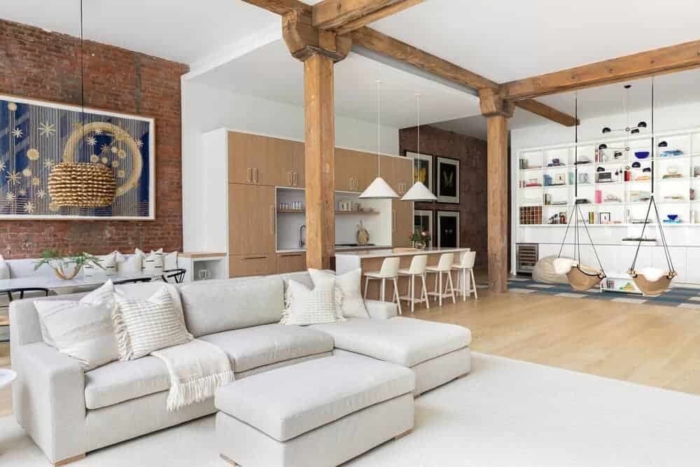 An open-concept room featuring a living space with a cozy sofa set, a dining area with a brick wall and an oval-shaped dining table set and a single wall kitchen featuring a breakfast bar island.