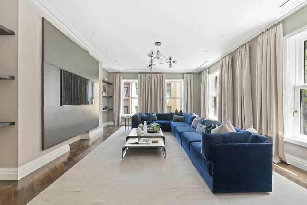 A velvet blue sectional stands out in this contemporary family room with gray walls, flat-screen TV, parquet flooring and a modular coffee table over a beige area rug. A modern glass globe chandelier completed the look.