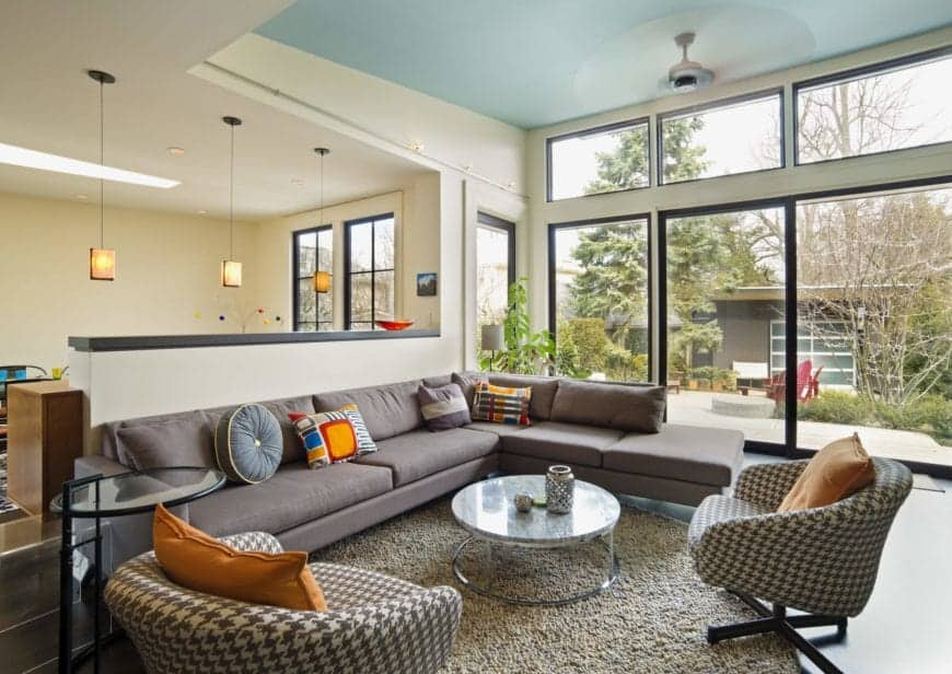 Charming living room with full height windows providing a refreshing view and natural light, sky blue ceiling with a fan hanging over an L-shaped sectional sofa and a pair of printed lounge chairs paired with a metal coffee table.