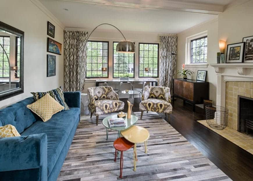Blue velvet sofa with a pair of printed fabric tub chairs and a multi-colored round nesting coffee table sits on a printed stripes rug facing the lovely brick fireplace.