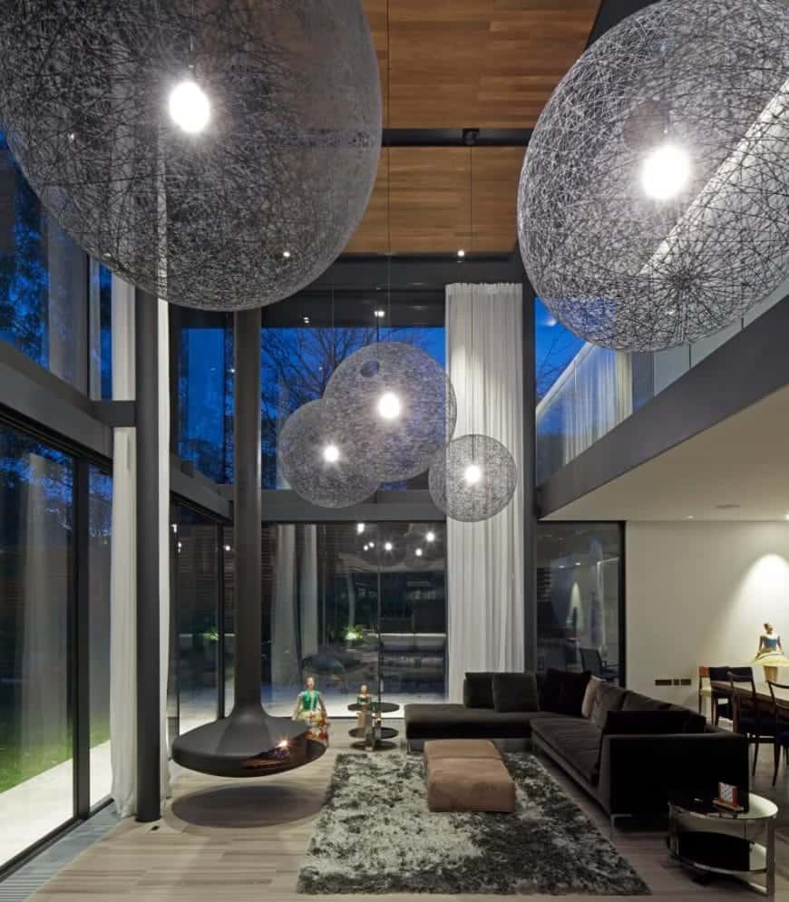 Huge Spherical rustic glam chandeliers hanging on a wooden ceiling illuminate the luxurious living room. Modern floating fireplace faces the black L-shaped sofa paired with a glass side table and brown ottoman that sits on a gray shaggy rug.