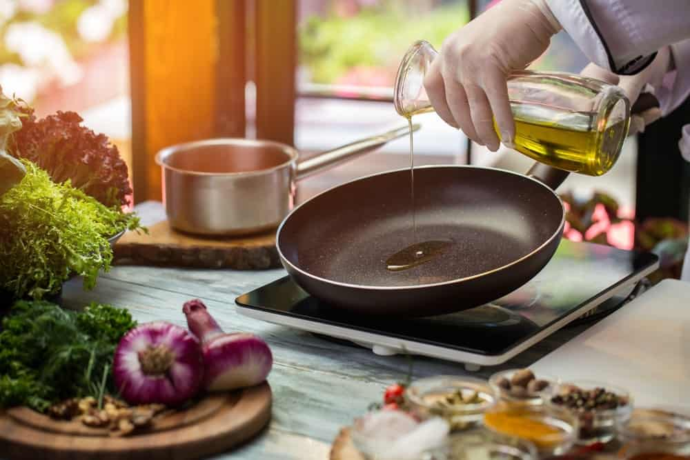 Pouring olive oil to a frying pan surrounded by green vegetables and onions.