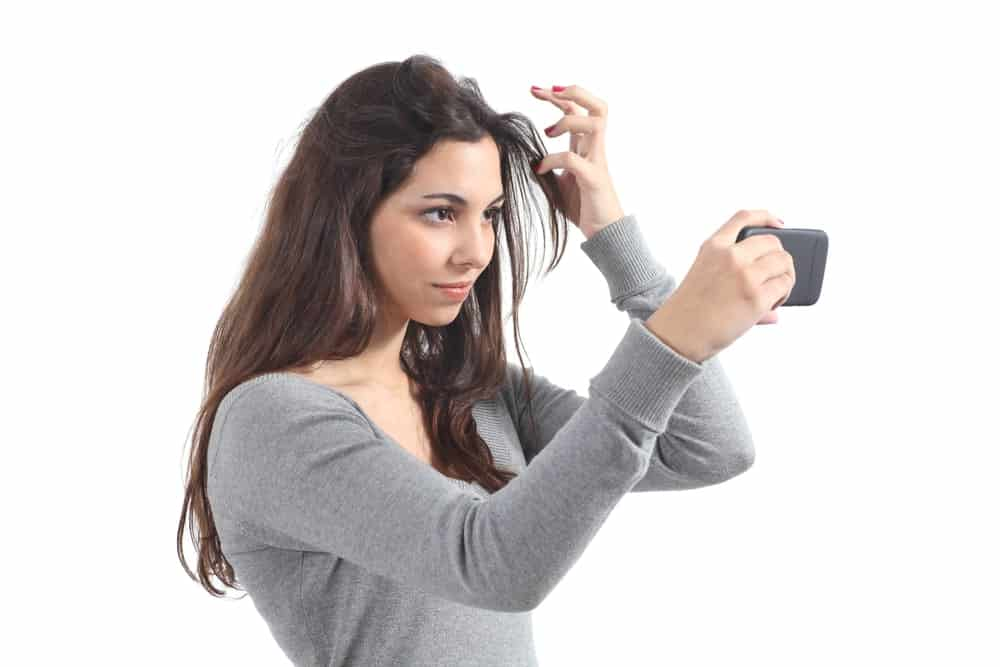 Woman primping her hair using a camera phone to check her reflection.