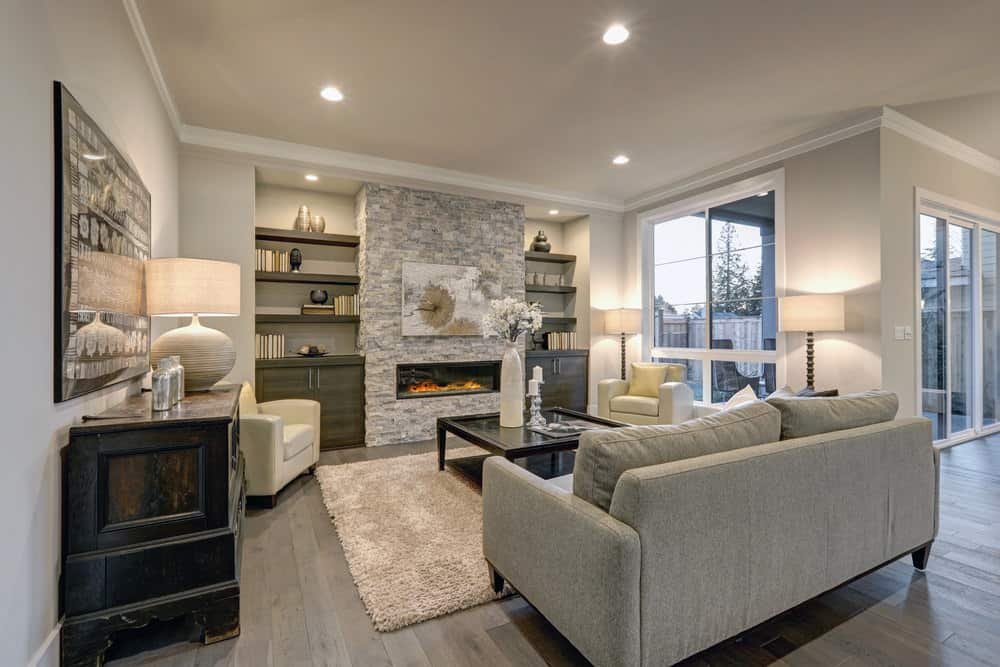 Whether it is a light or dark gray room, it needs a little warmth, and it can easily be accomplished with warmer tones in the furniture, which is achieved here through a dark wooden table and darker gray cabinets in this living room design.