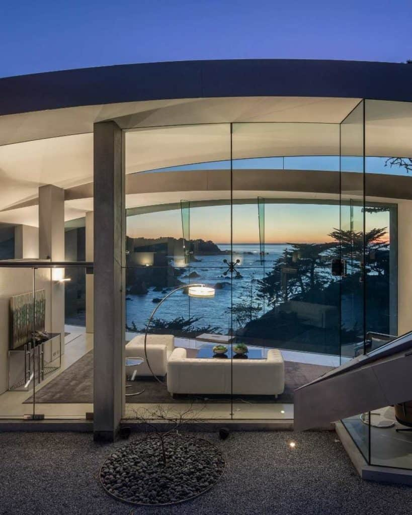 Incredible modern living room with towering all glass walls front and back overlooking the ocean