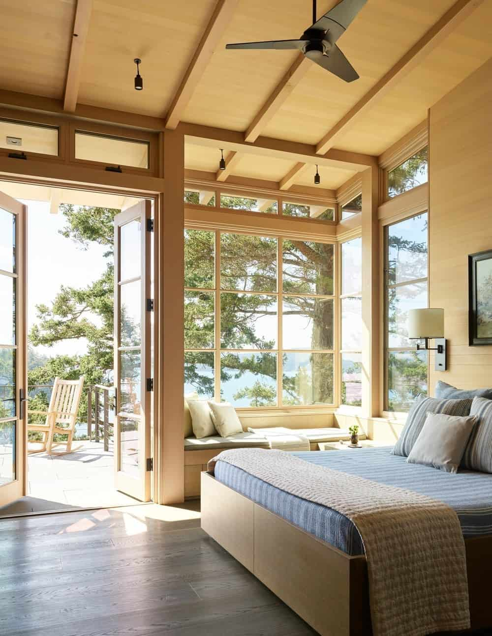 I love this contemporary primary bedroom with high wood ceiling and fabulous reading window nook with double doors to a deck with view of the lake.