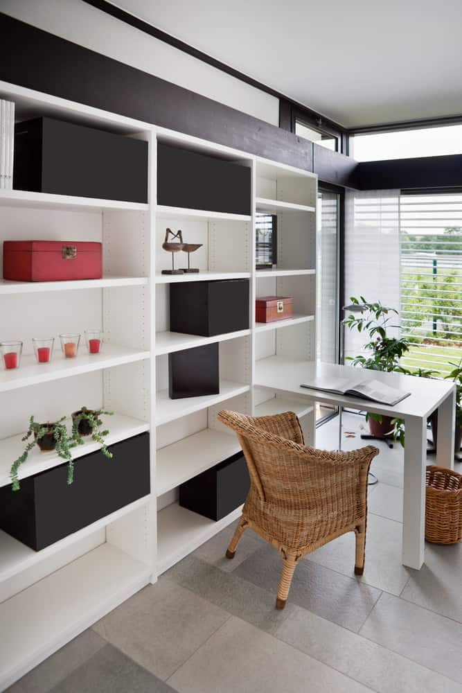Simple home office with built-in open shelving for plenty of storage and an attached space-saving built-in desk paired with a wicker armchair and wastebasket.