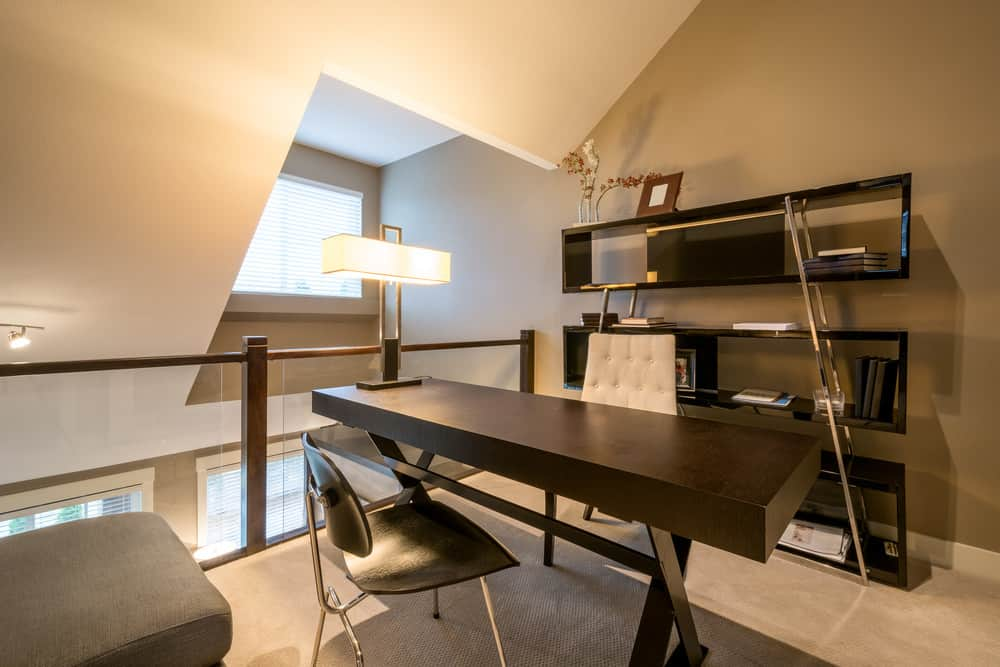 Attic home office with freestanding open shelving, a long rectangular office table, and a stylish lamp.