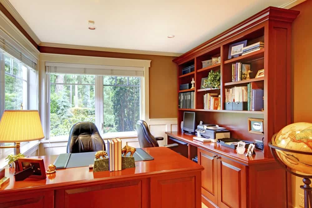 Home office with wooden furniture and large windows.