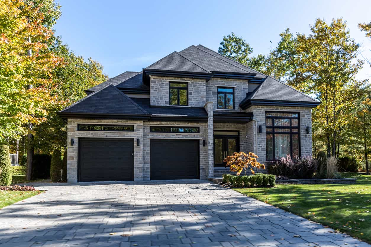 This stunning brick house seems to have a hip roof on all of its rooms. The walls of the house are made of brick in pale neutral shades of beige, but the hip roof uses a dark shade of gray, bring the house to life. This house looks very majestic and imposing.