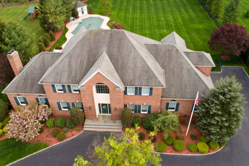Aerial view of large house with a complex hip roof