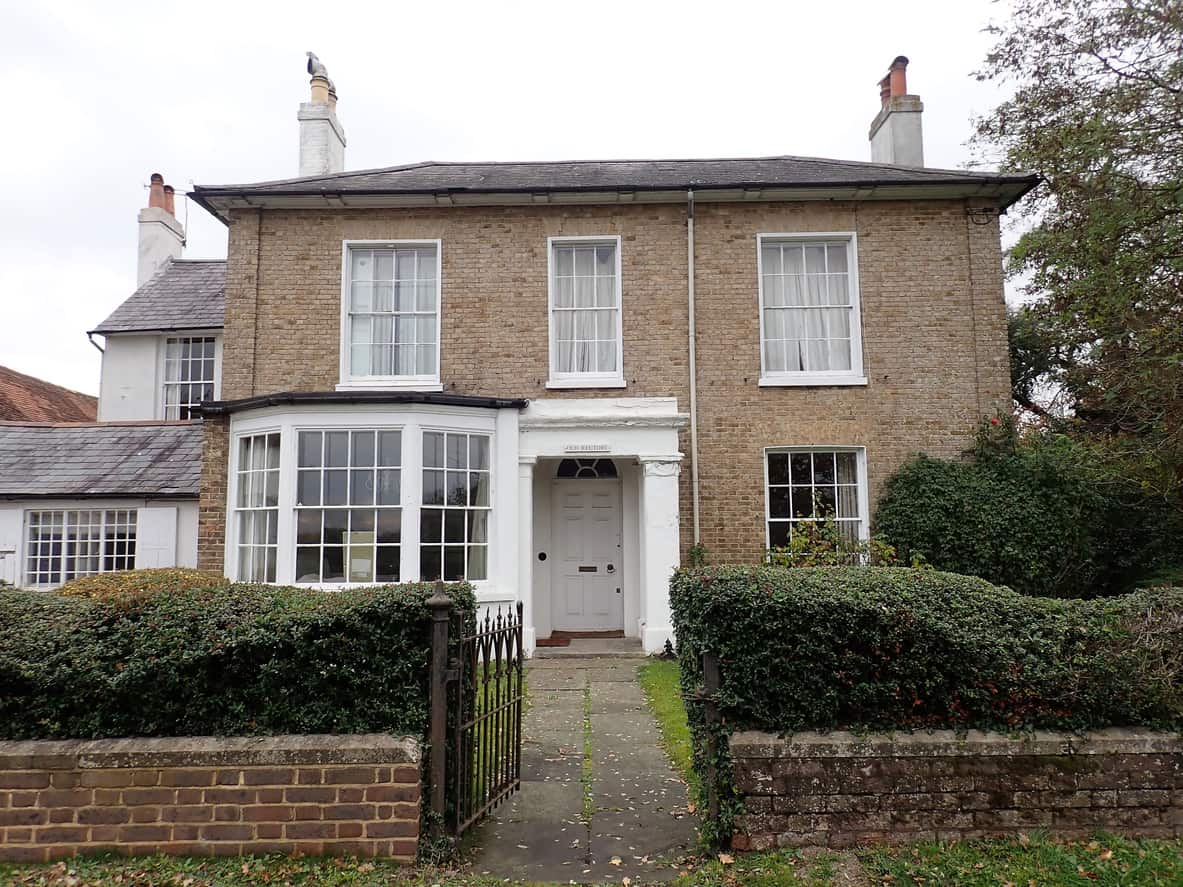 This mansion is a classic example of Georgian architecture, characterized by a low-angled hip roof. The house is made of small bricks that were once so popular. With its white stenciled windows and columns of chimney, this house seems to take you back to 18thcentury England.