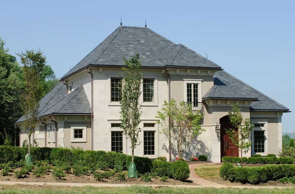 This cream and grey colored house is one of the best looking houses with hip roofs that we have seen. The cool gray color of the hipped roof counterbalances nicely with the pale creamy shade of the walls. The neutral shades are offset by a dark red door that lends a pop of color to this beautiful house.