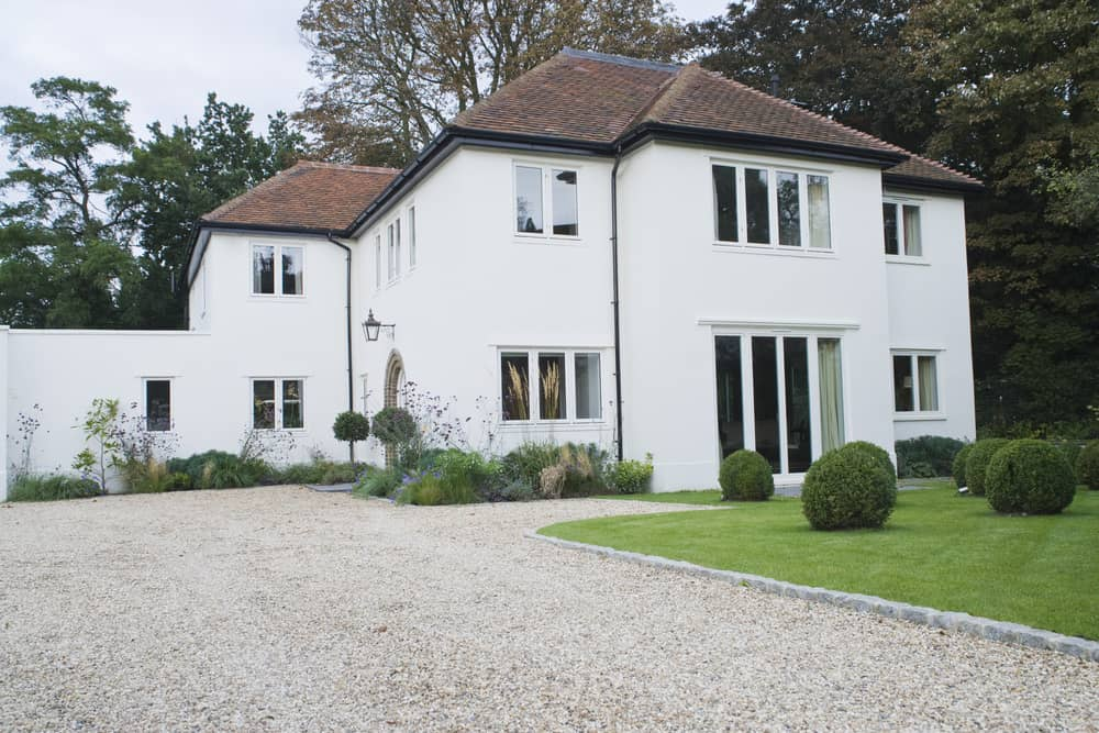 The pure white walls of this house contrast beautifully with the earthy brown tones of the hipped roof. The house has an elegant country house type of look and the high walls make it quite majestic. This could be a great home for some well-to-do farmers or lovers of the countryside.