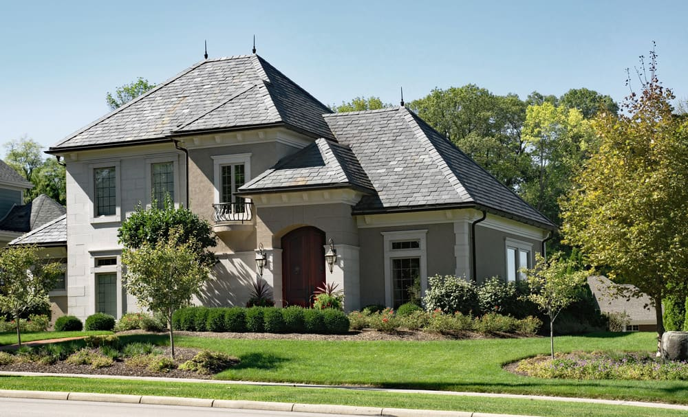 The house is comprised of pale gray walls with only one section a warm shade of beige. Silver-gray hip roof tower above the building. With its beautifully manicured lawn and bushes, this house is a perfect place to throw a garden party.