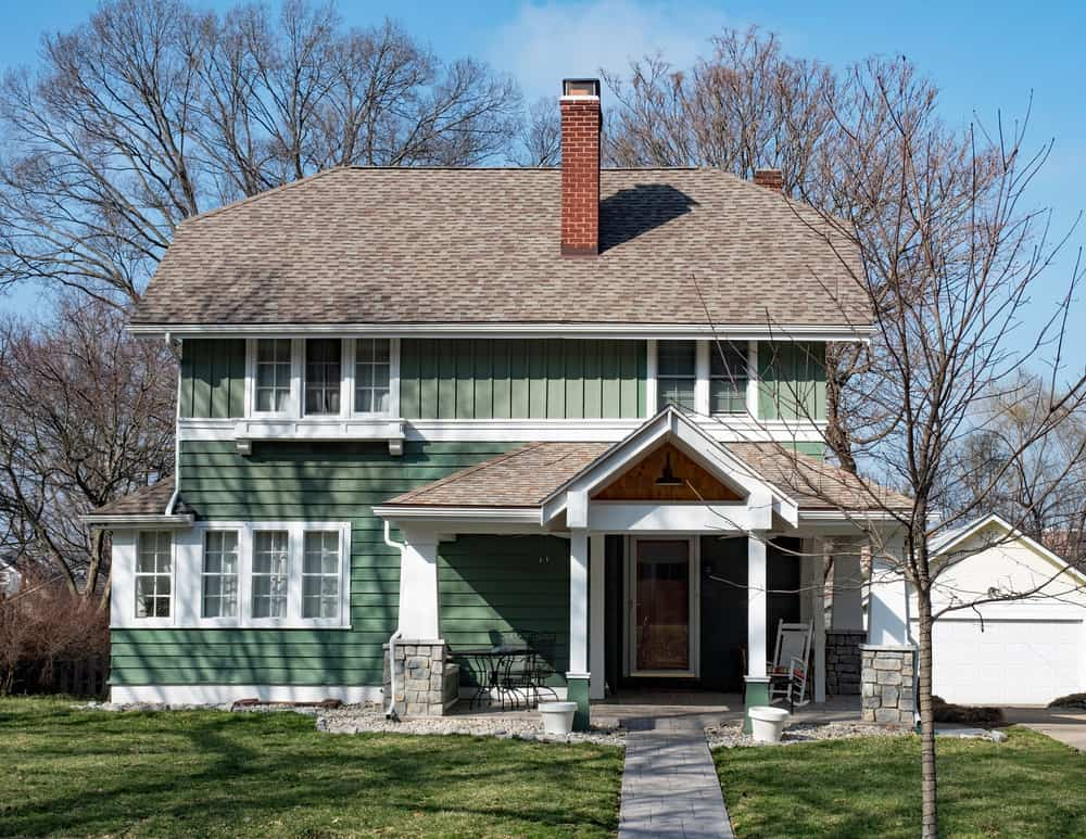 This lovely house looks extremely cozy and comforting. The house is characterized by a half-hipped roof with a brick chimney. What sets is apart from other houses is the pastel green colors of its wooden wall and the gabled entrance to the house. this looks like a great place for a winter retreat.