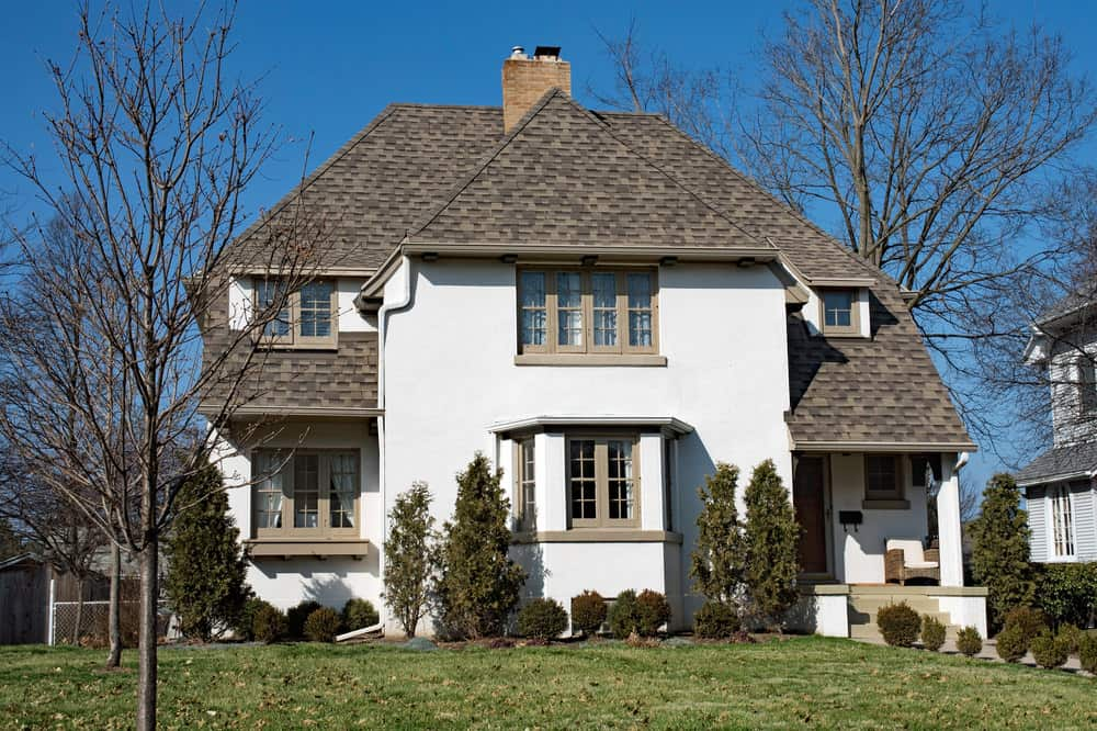 The white walls of this house are balanced by the warm, rustic brown colors of the hip roof. This quaint house looks like it belongs near a large farmland. It also exudes a colonial aura because of its peaked roof design.