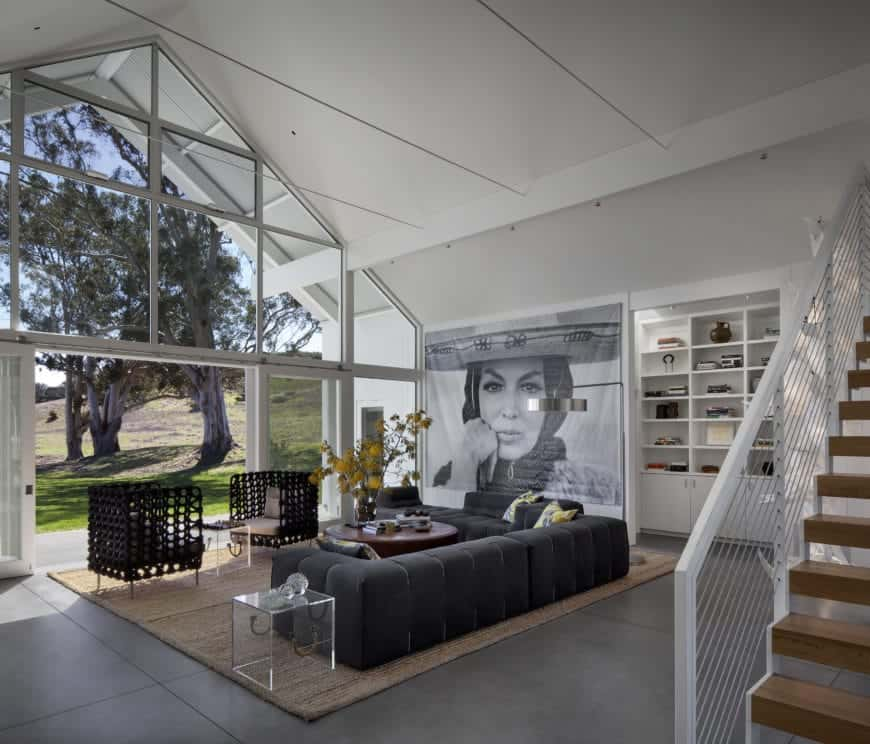 A unique living room with cathedral ceiling, black L-shaped sofa with a pop of yellow complementing the plant that sits on a wooden coffee table, a glass side table and a pair of black rattan lounge chairs with cushions over a brown rug. Glazed walls naturally light the house while a huge lovely portrait adds personality to the room.