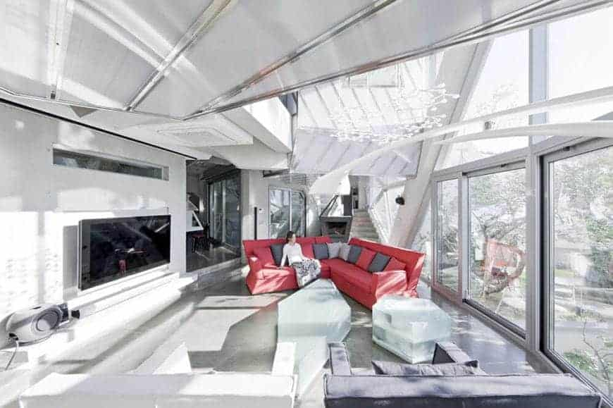 A red V-shaped sofa with back pillows stands out from the spacious white and gray tone living room. It is decorated with contemporary furnitures and hanging ornaments.