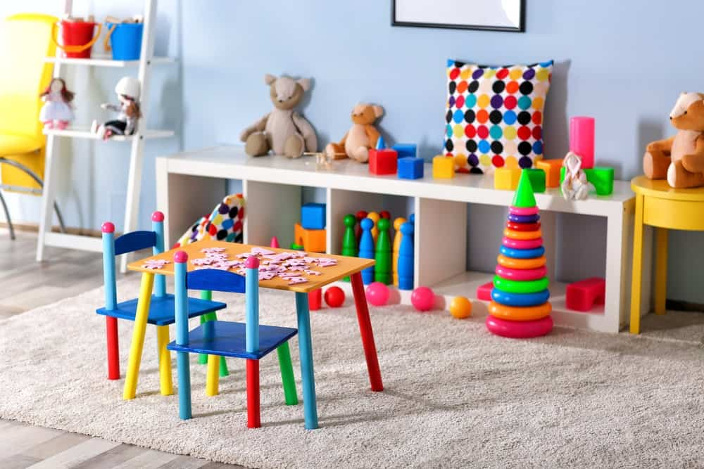 Indoor playroom furnished with low shelves, kid-sized table and chairs, and various toys.
