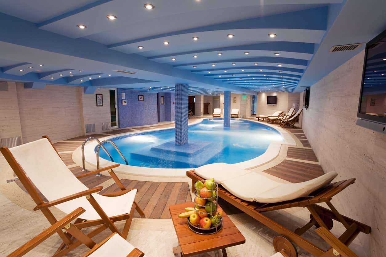 This indoor swimming is pure sophistication and elegance at its best. With sky blue ceiling, small round yellow lights, and wooden relaxing chairs on either side, you might just feel like you are in a pool in Hawaii.
