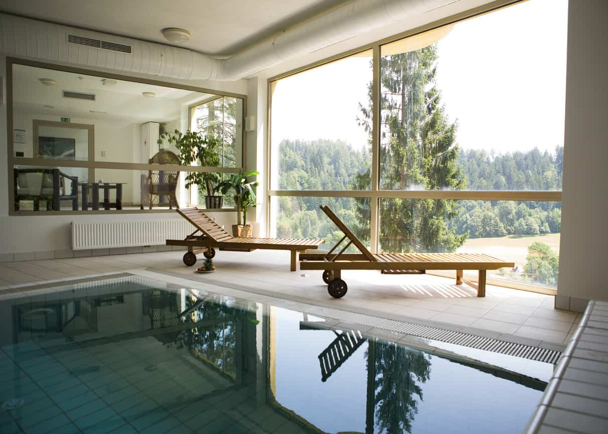 From a stunning outdoor view to a pretty interior, this indoor swimming pool has almost everything but in moderation. With huge windows and two simple relaxing wheeler chairs, this is the epitome of simple yet stylish.
