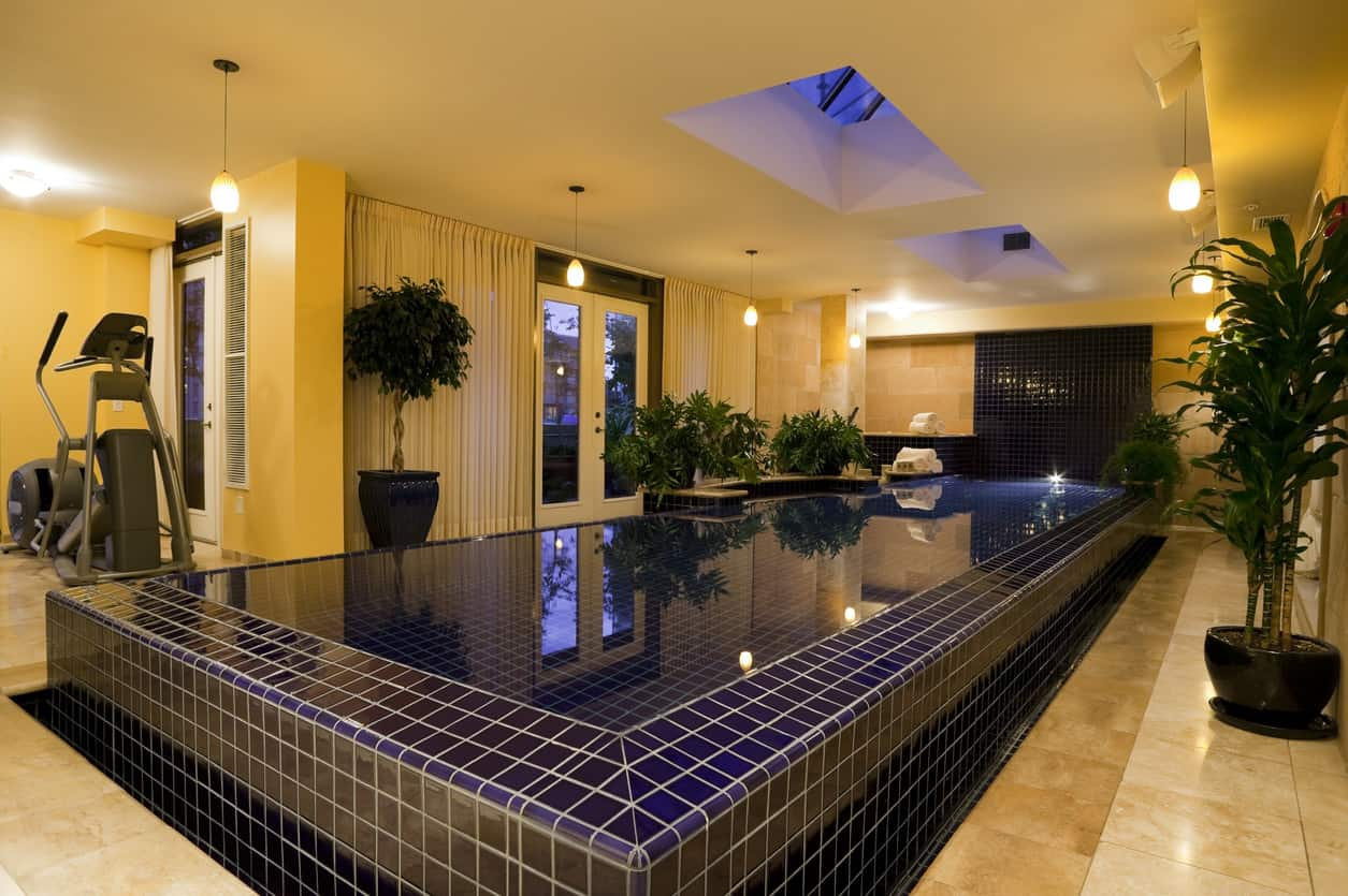 This indoor pool looks like it has come right out of the movies. With checkered swimming pool walls, dark green lush planters all around, and yellow-golden tones of light illuminating the whole area, it is just perfect and mystical.