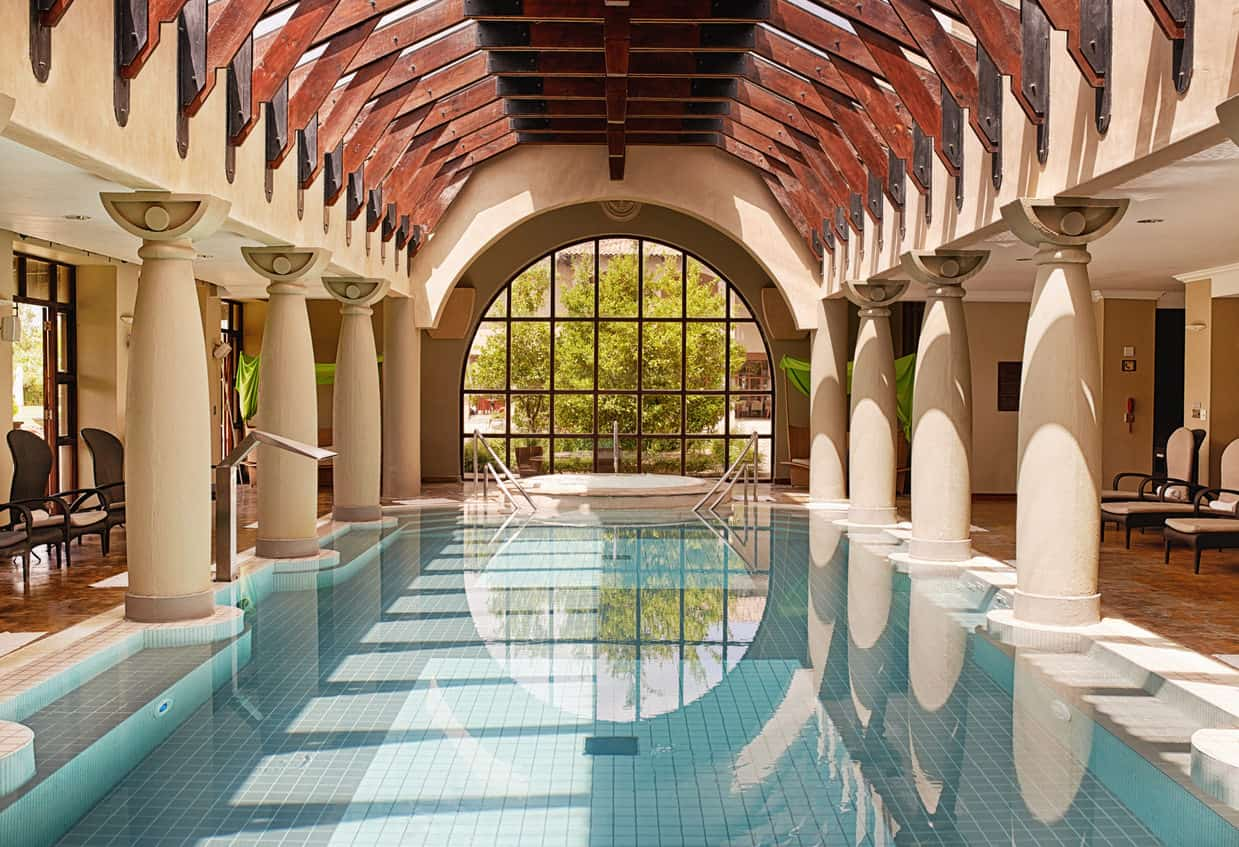 Huge pillars, fancy wooden ceiling and a massive view into the nature through a dome-shaped glass window, this swimming pool looks like it is right out of the ancient Roman era.