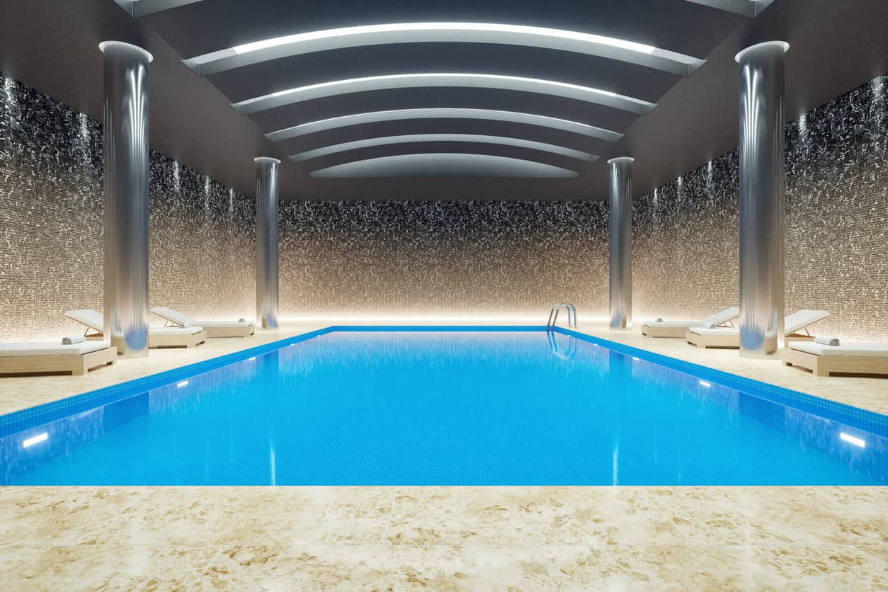 If fancy and glittery is your style, this swimming pool is an excellent choice for you. It has super stylish and sleek silver pillars on both sides, supporting similar silver ceiling with lines-like spaces that allow the glistening sunshine to pass through. On either sides of the pool there are those relaxing chairs like the ones you find at the beach, giving you slight beach-like feels.