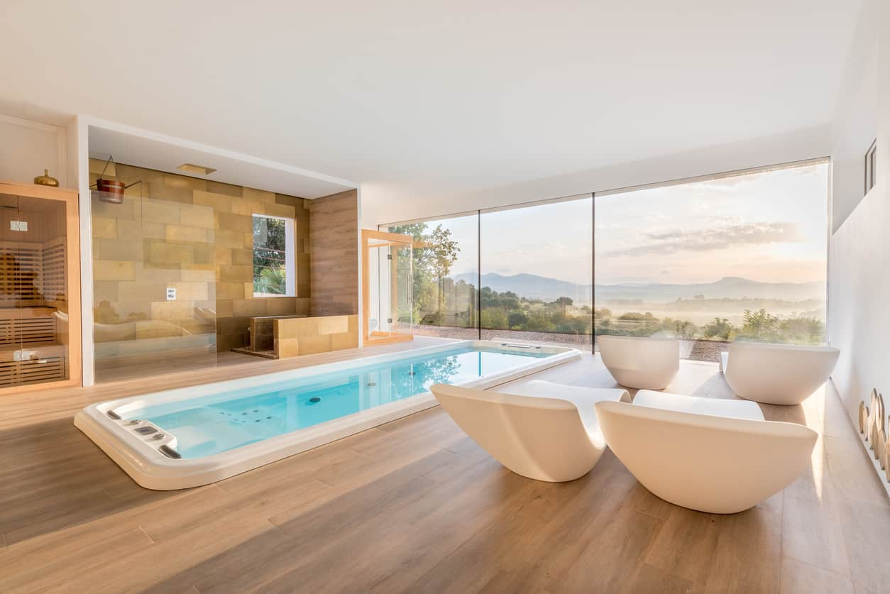 For someone who loves to have their indoor pool in a huge space, this design is for them. This is quite a small pool in a huge wooden space with wooden floors and four stunningly white seaters for you to relax after you are done swimming.