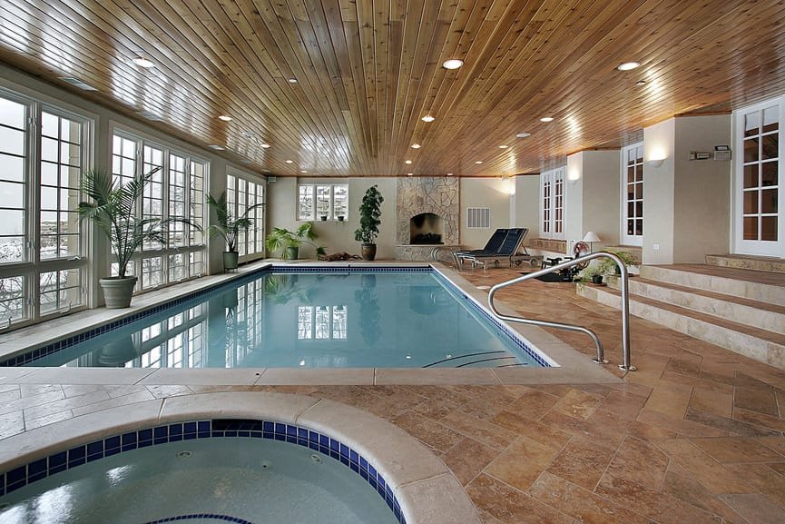 A brown interior always pairs well with an indoor pool, just like this one. It is quite a lavish affair with a huge swimming pool and surrounding windows that let you look at nature and experience an outdoor-like feeling.