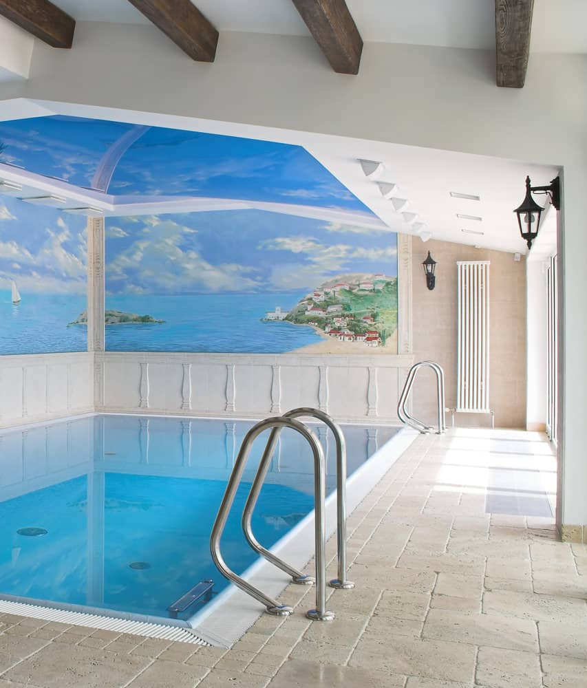 This indoor swimming pool looks like one of those that are typically found in farmhouses. It is a simple pool with white exterior, and a huge window all the way to the ceiling, providing a gorgeous outdoor view.