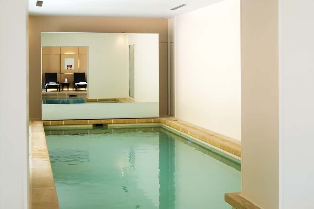 Small and simple is a suitable description for this indoor pool with a mirror in the front and a full white interior.
