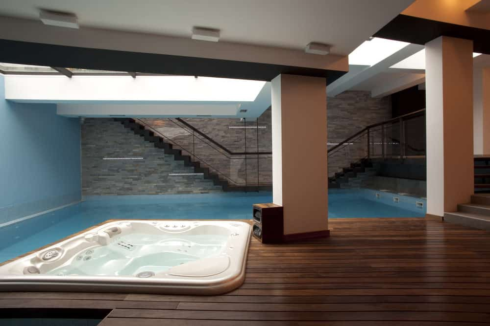 A brilliantly unique indoor pool idea, this is simply gorgeous. Situated right under the stairs with white pillars and wooden designed ceiling, this pool is the definition of different and chic.