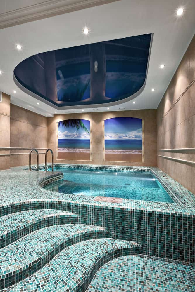 Simple and chic, this indoor swimming pool sports a common pool-theme that you would often find in swimming pools with tiled stairs leading into the pool. All this has been taken to a new level with a fancy ceiling and two small windows that allow one to look outside.
