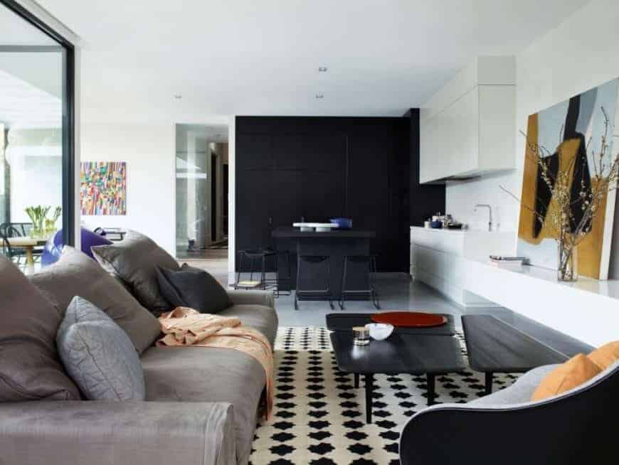 lassic living room that shares the same space with the dining area. It has an interesting three-piece coffee table that sits on a white and black patterned rug paired with a brown sofa and a cuddle chair.