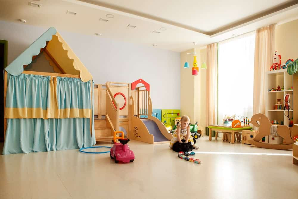 Young girl playing in a spacious kid's playroom.