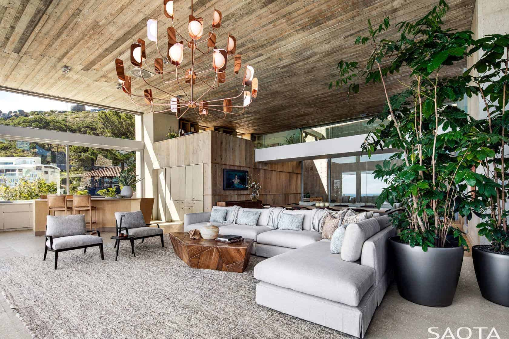 A living room that gives you warmth and a rustic feel. It features a huge statement chandelier hanging on a light-colored wooden ceiling, a gray L-shaped sectional sofa with a wooden center table over a gray shaggy rug and two large indoor plants that add life to the room.