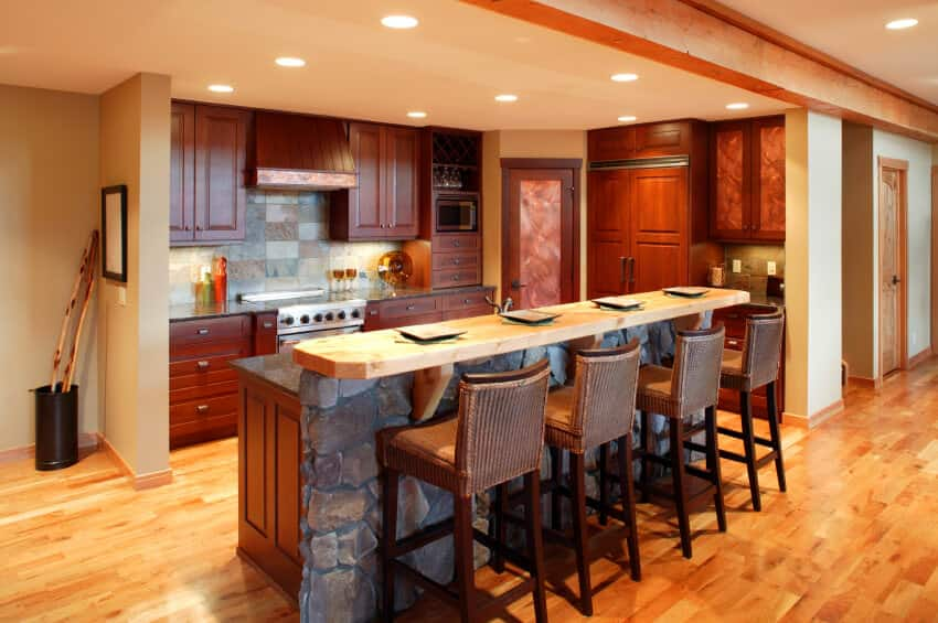 This kitchen leaves no shade of brown unused. The floor hold a shade of hazelnut and the cabinets the shade of walnut, the kitchen also features an oak panel running atop the ceiling. The mosaic of stone tiles in the backdrop and the stone wall at the counter give the room a rustic feel.