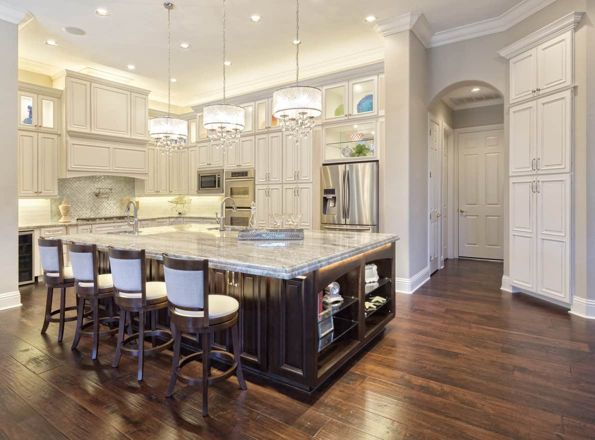 This kitchen speaks beauty and style with a range of kitchen appliances all embedded in the walls and white cabinet panels with the chocolate-brown two-toned floor. Seating for All