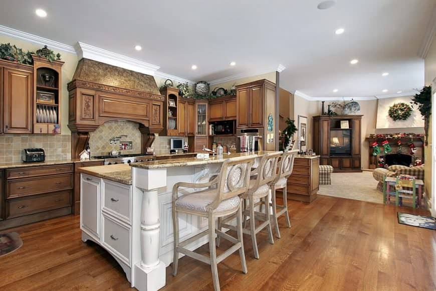Heavily designed chairs, a giant kitchen island, and caramel colored wooden cabinetry that matches the floor perfectly – this kitchen doesn't go overboard with furnishings. It's just very grand and striking. After all, a little pomposity doesn't hurt.