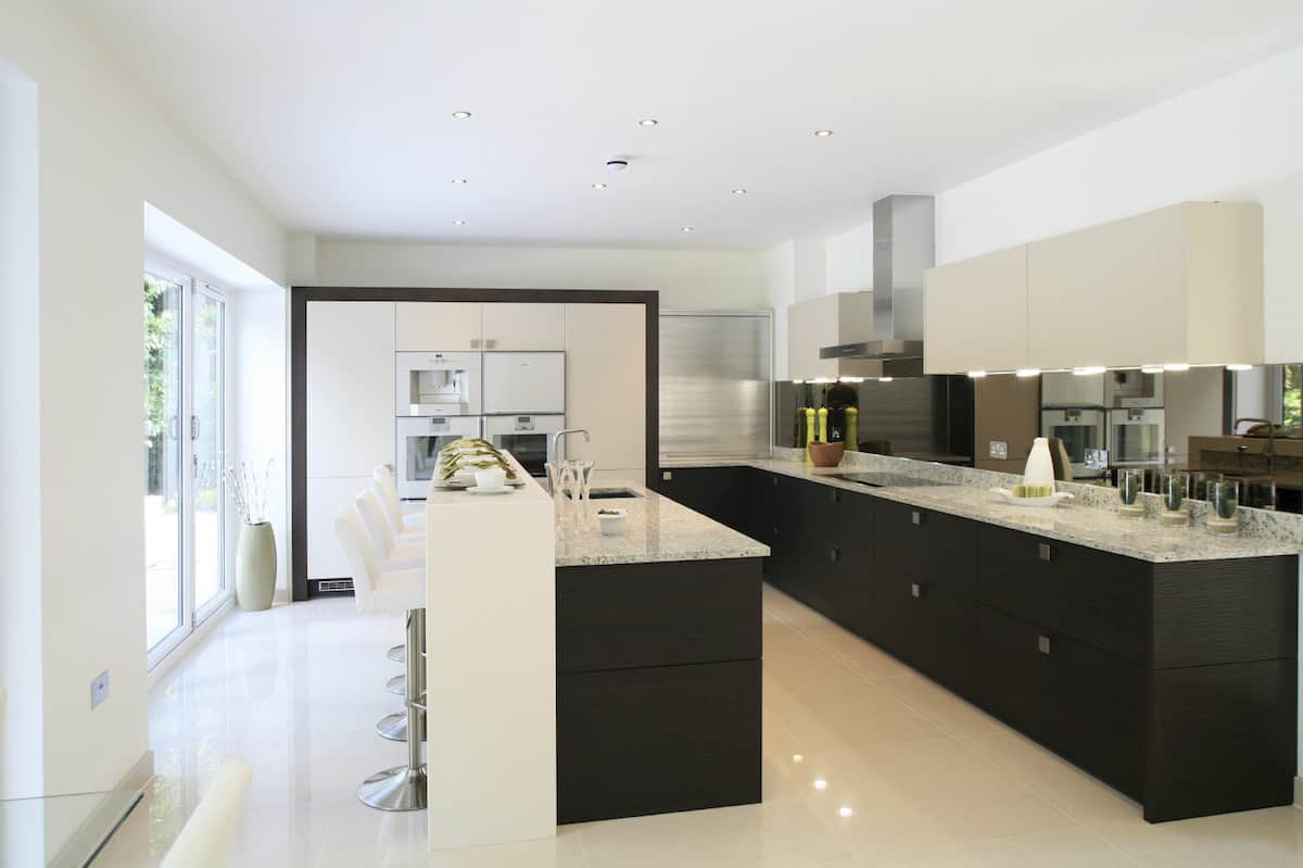 This L-shaped kitchen makes a lasting impression with its symmetrical design. Two long counters run along the space. Spotless white floor with a high gloss finish and speckled marble tops reflecting the light from under-the-cabinet fixtures take this space way beyond neat.