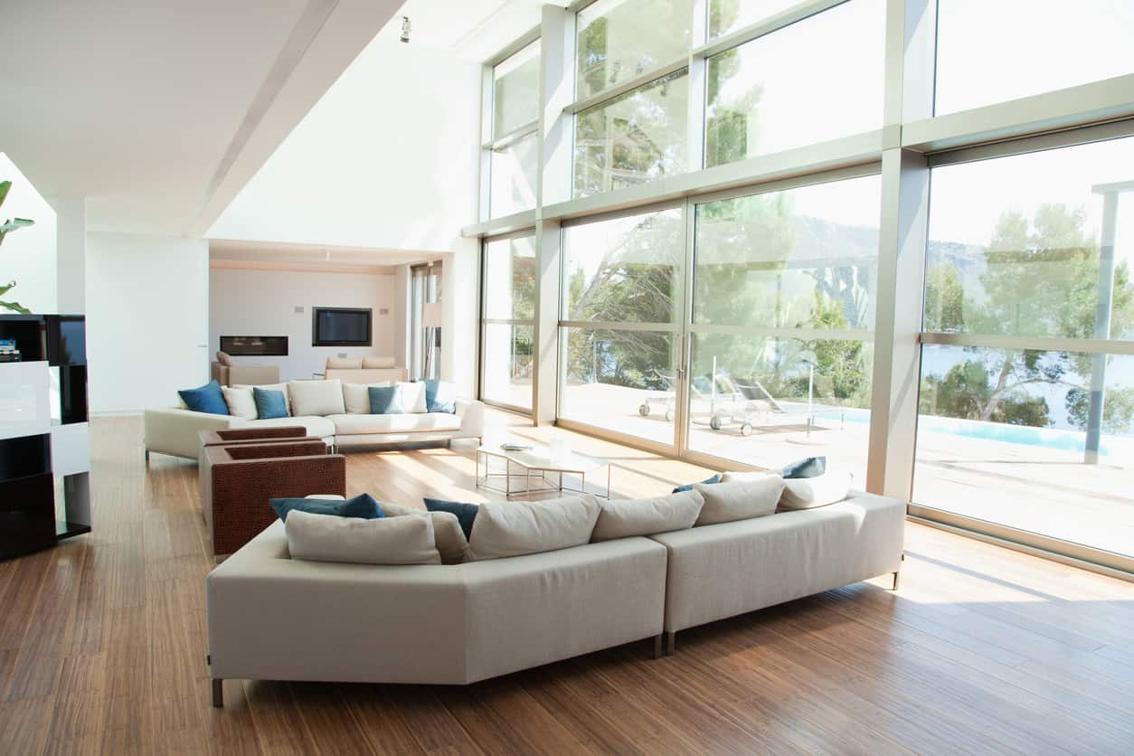 A large, contemporary living room with floor to ceiling windows and neutral toned hardwood floors is finished up with blue accent cushions.