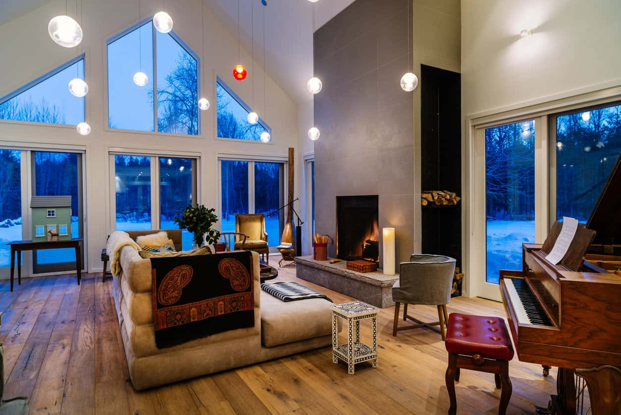 A contemporary cabin with sleek design uses rustic hardwood floor and furniture to give a nod to classic cabin furniture.