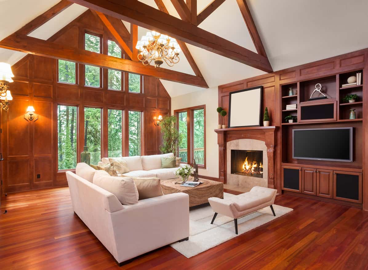 A Simple but cozy cabin with dark cheery colored wood flooring and paneling blends with the simple neutral colored furniture. This is a great example of the flooring making the furniture look better than its already stunning aesthetic.